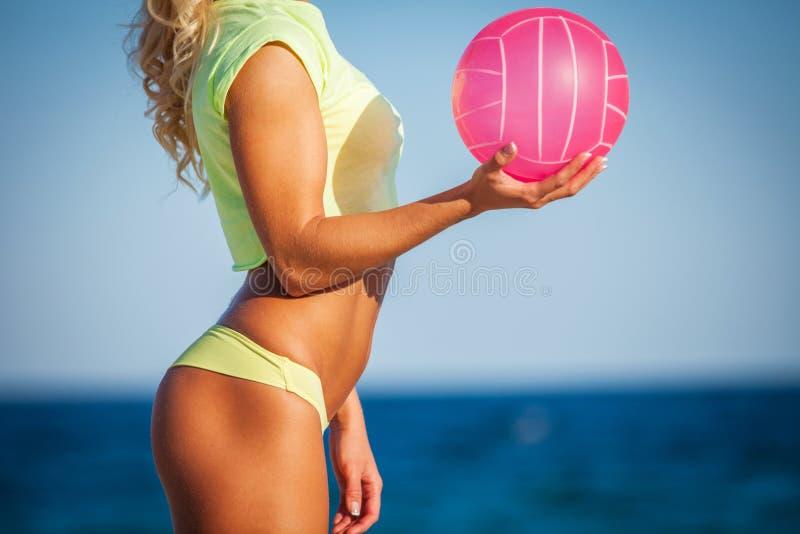 Mujer en el bikini que lleva a cabo un voleibol imágenes de archivo libres de regalías