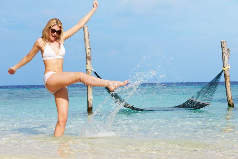 Mujer en el bikini que salpica en el mar tropical hermoso fotografía de archivo libre de regalías