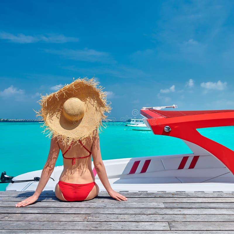 Mujer en el bikini que se sienta en el embarcadero con el barco imagen de archivo