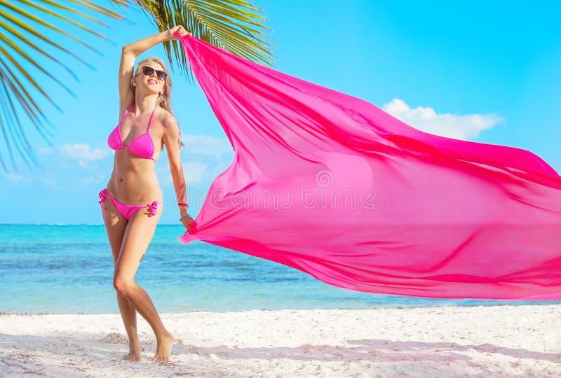 Mujer en el bikini rosado que sostiene la tela rosada en viento en la playa tropical foto de archivo libre de regalías