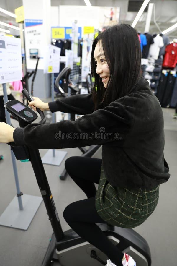 Mujer en el bycicle interior que completa un ciclo en gimnasio Competencia, caucásica imagen de archivo