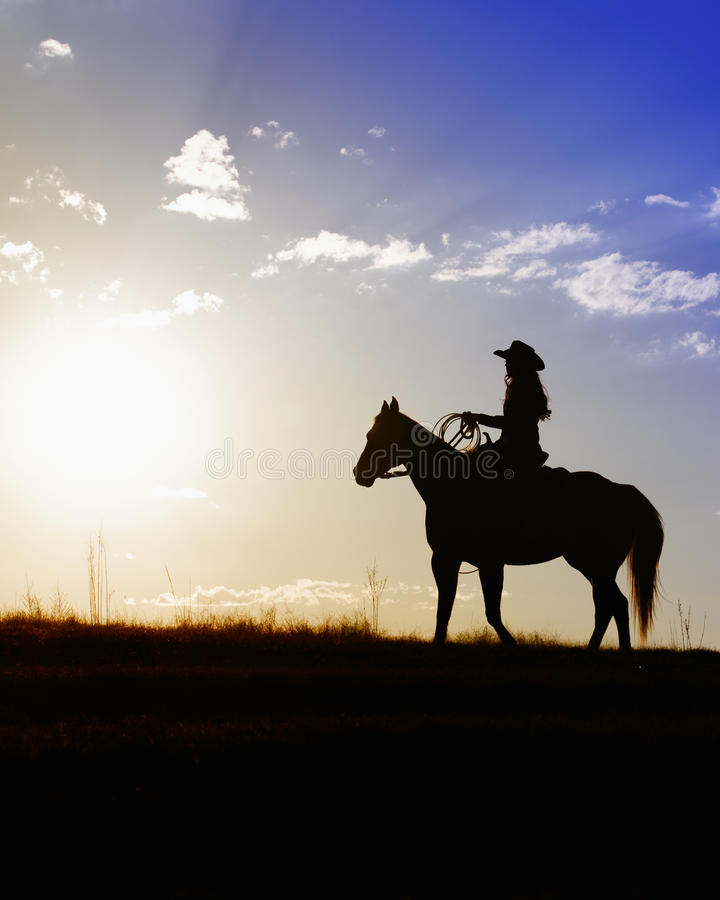 Mujer en el caballo que mira puesta del sol hermosa imagen de archivo libre de regalías