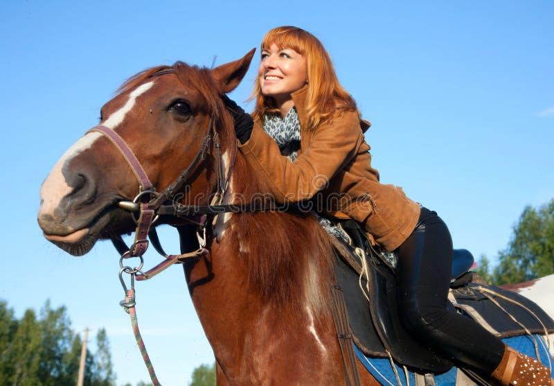 Mujer en el caballo rojo imagen de archivo