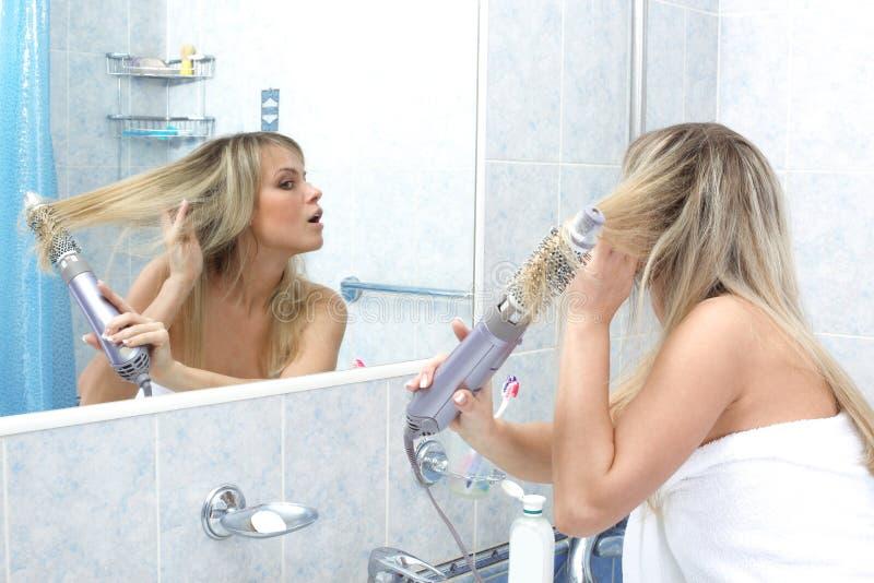 Mujer en el cabello seco del cuarto de baño fotografía de archivo libre de regalías