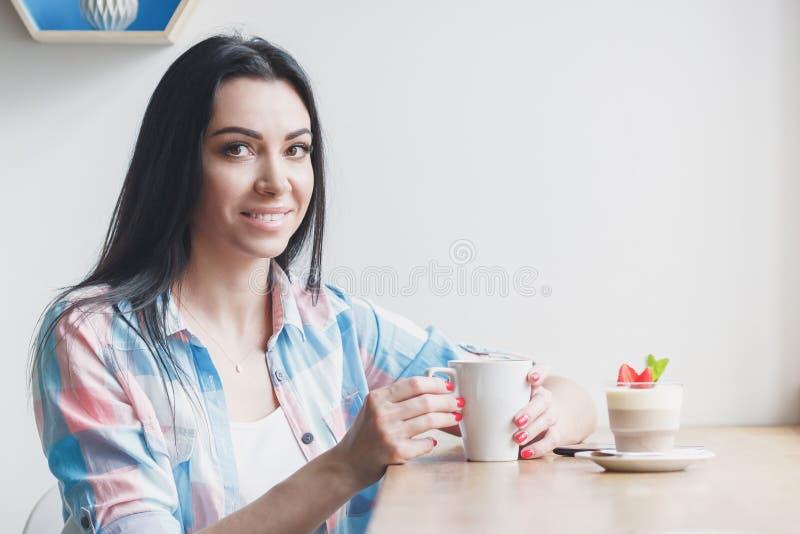 Mujer en el café con una taza de postre del café y de la fresa foto de archivo libre de regalías