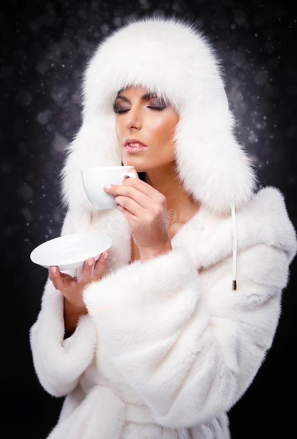 Mujer en el café de consumición blanco del abrigo de pieles y del casquillo foto de archivo libre de regalías
