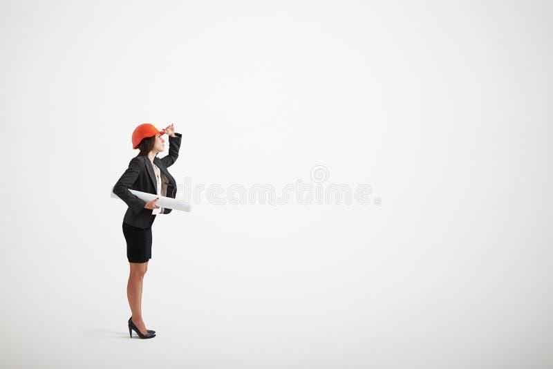 Mujer en el casco del desgaste formal y de la construcción que sostiene modelos imagen de archivo libre de regalías