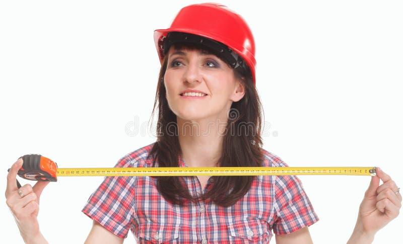 Mujer en el casco que lleva a cabo una cinta métrica imagen de archivo libre de regalías