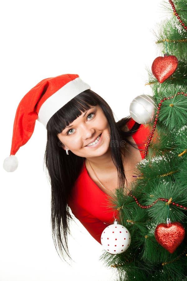 Mujer en el casquillo rojo que mira fuera del árbol de navidad imagen de archivo