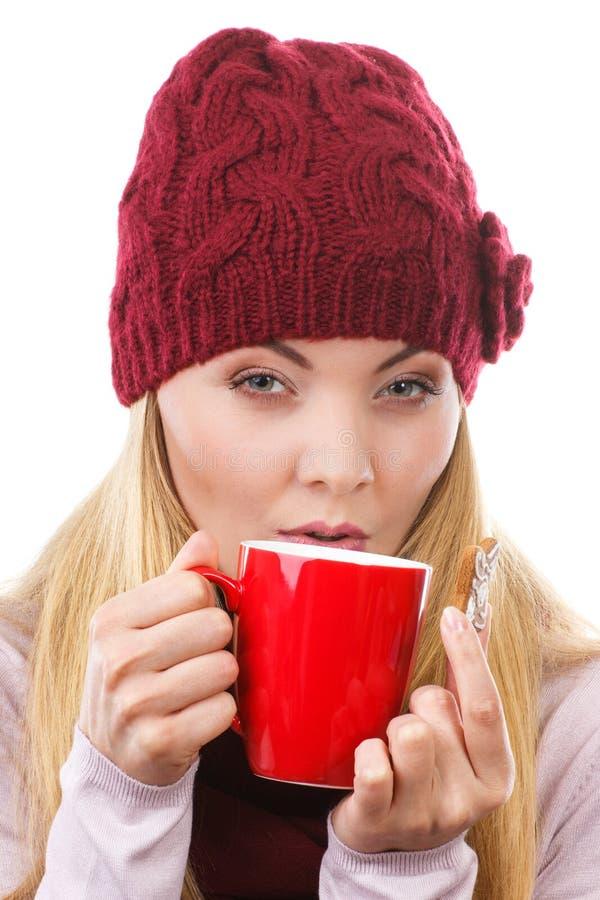 Mujer en el casquillo y el mantón que sostienen el pan de jengibre y la taza de té caliente, tiempo de la Navidad foto de archivo