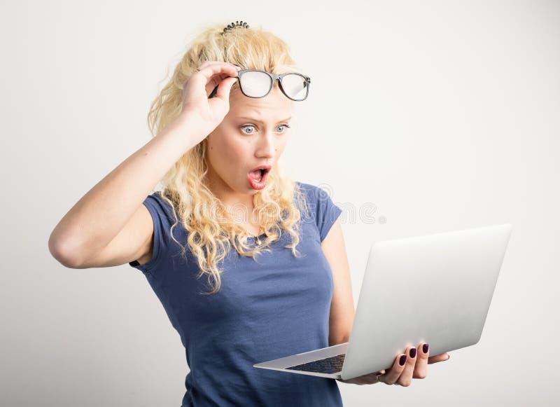 Mujer en el choque que mira el ordenador portátil imagen de archivo