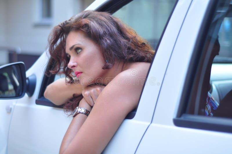 Mujer en el coche blanco que parece agujereado imágenes de archivo libres de regalías