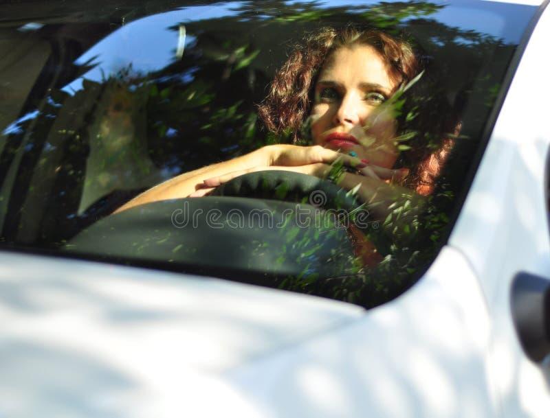 Mujer en el coche blanco que parece agujereado imagen de archivo libre de regalías