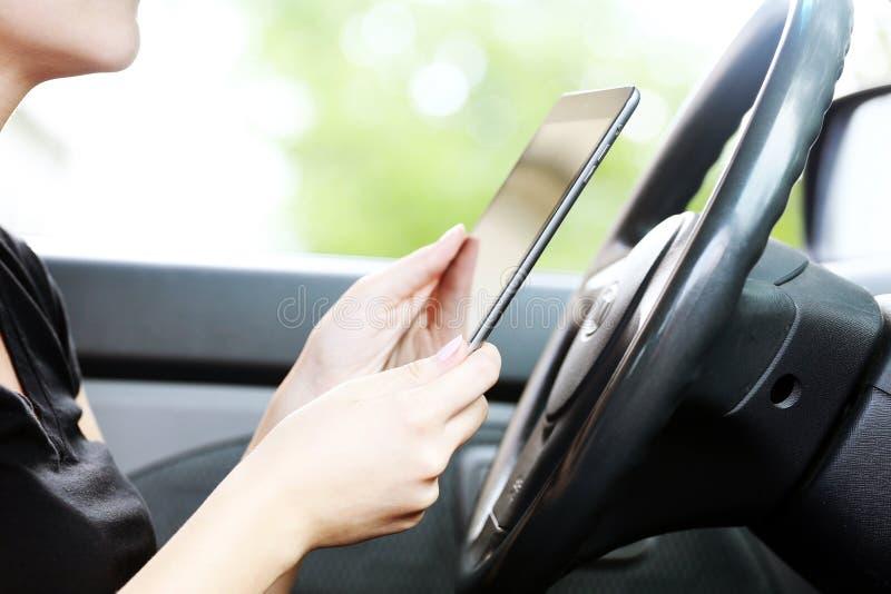 Mujer en el coche con PC de la tableta fotografía de archivo