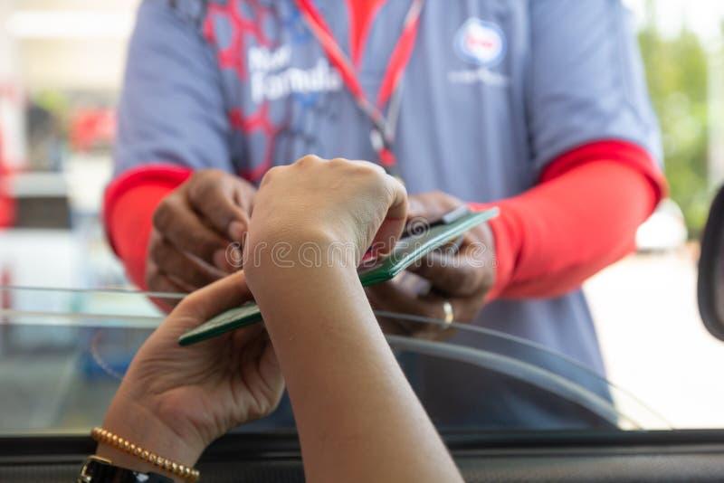 Mujer en el coche que paga la gasolina con la tarjeta de crédito, pago femenino de la tarjeta de débito que se sostiene en la gas foto de archivo libre de regalías