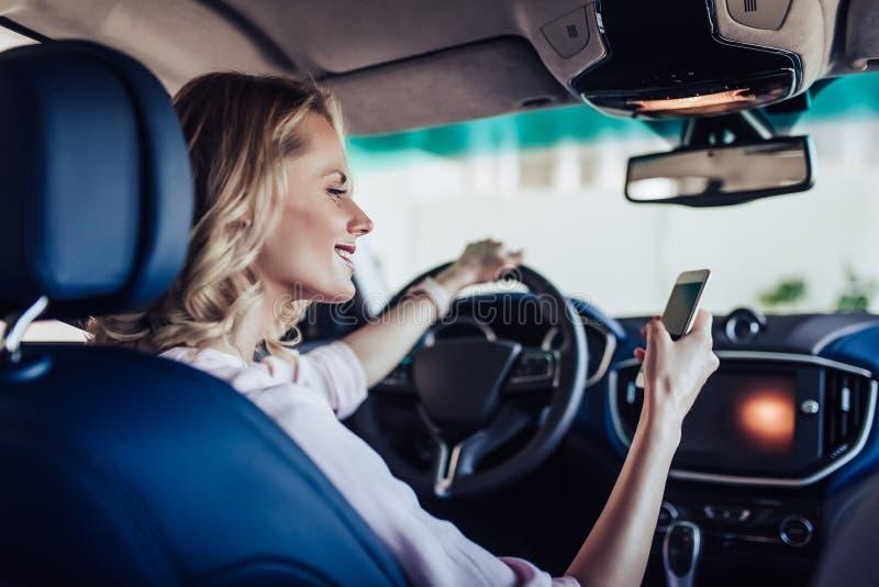 Mujer en el coche usando smartphone fotografía de archivo