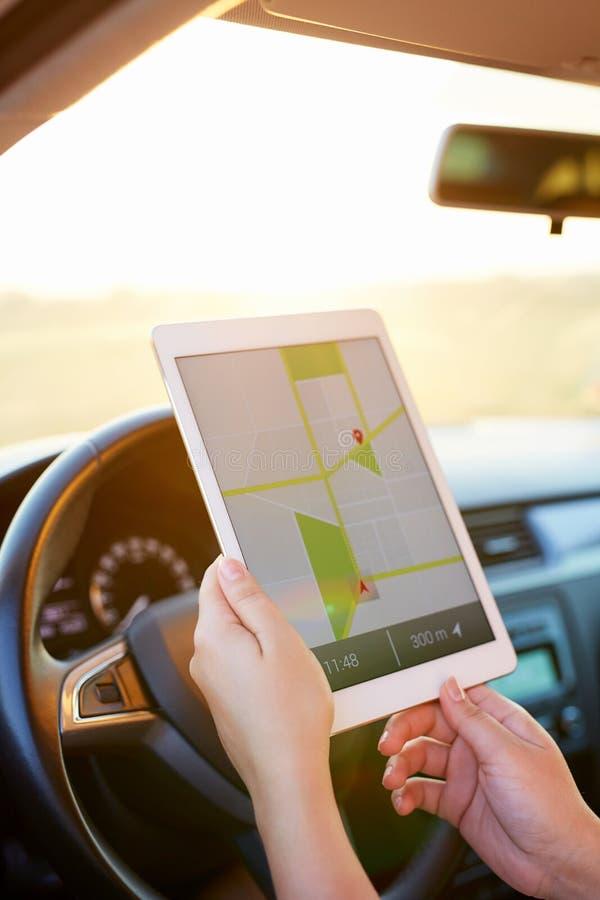 Mujer en el coche y la tableta el sostenerse con la navegación de los gps del mapa imagen de archivo libre de regalías