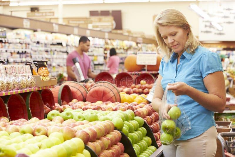 Mujer en el contador de la fruta en supermercado foto de archivo