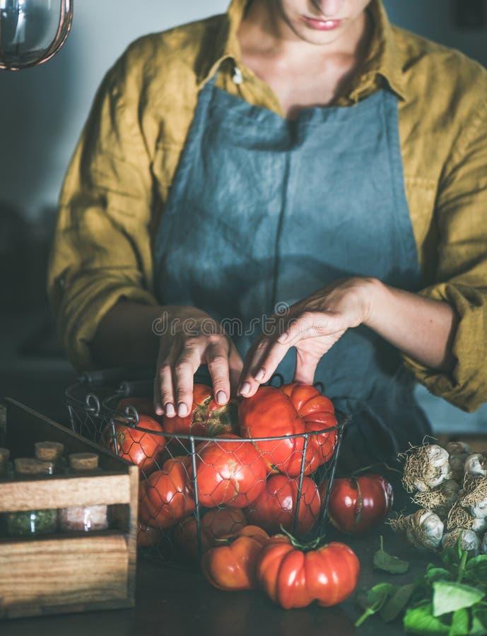 Mujer en el delantal de lino que saca los tomates de cesta imagen de archivo