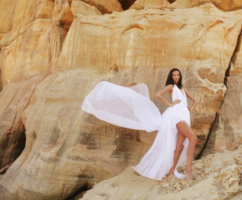 Mujer en el desierto sobre fondo de la arena imágenes de archivo libres de regalías