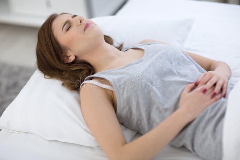 Mujer en el dolor que miente en la cama fotografía de archivo libre de regalías