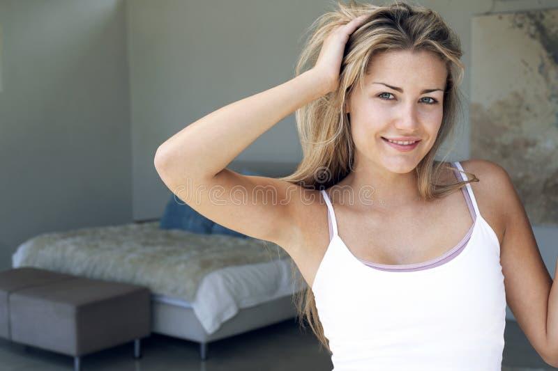 Mujer en el dormitorio que despeina el pelo fotos de archivo libres de regalías