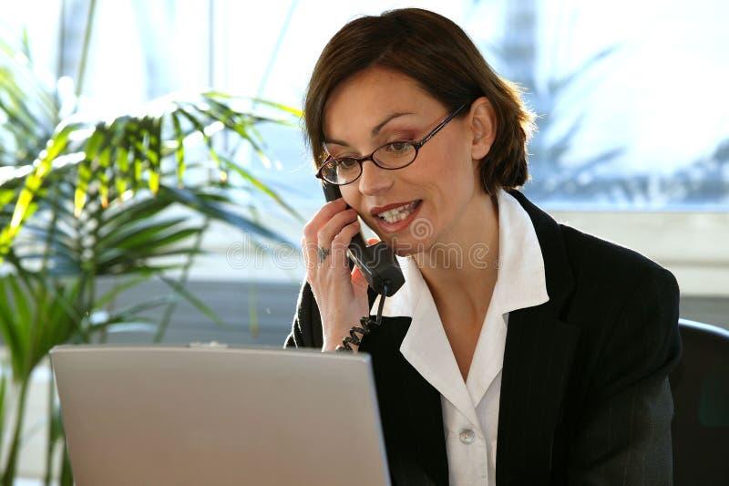 Mujer en el escritorio con el ordenador portátil y el teléfono fotos de archivo