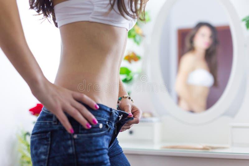 Mujer en el espejo en el sujetador blanco y vaqueros foto de archivo