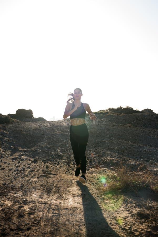 Mujer en el funcionamiento negro en un camino de la arena imagen de archivo libre de regalías