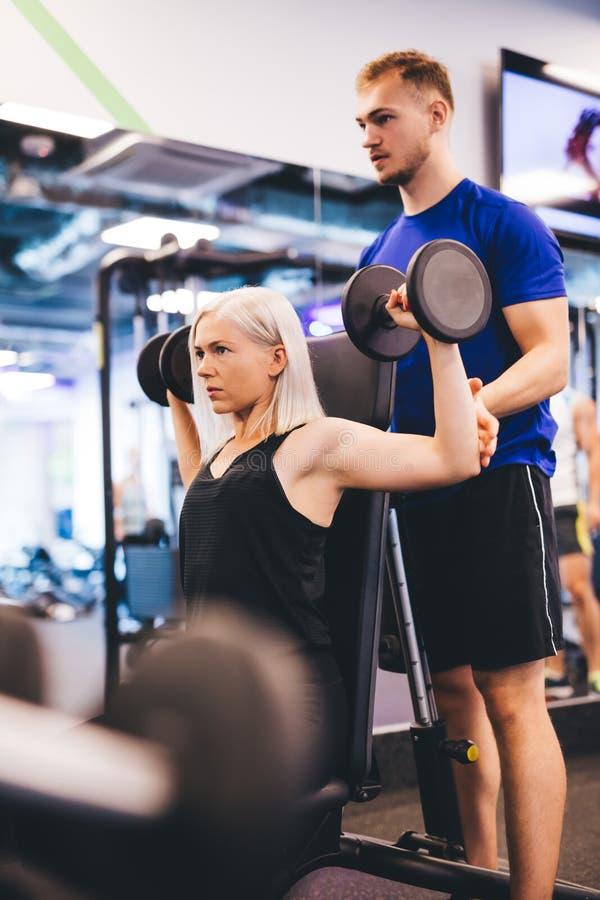 Mujer en el gimnasio que ejercita con el instructor personal imagen de archivo libre de regalías
