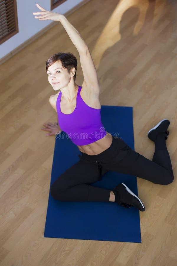 Mujer en el gimnasio que hace ejercicios en la estera foto de archivo libre de regalías