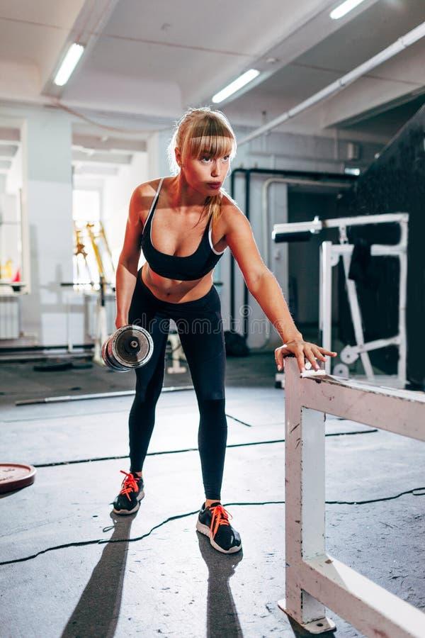 Mujer en el gimnasio que hace sola fila de la pesa de gimnasia del brazo fotos de archivo