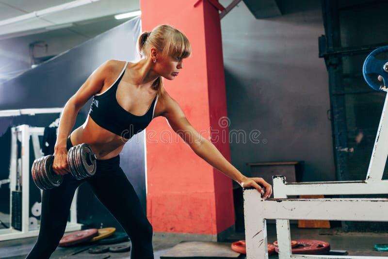 Mujer en el gimnasio que hace sola fila de la pesa de gimnasia del brazo imagen de archivo libre de regalías
