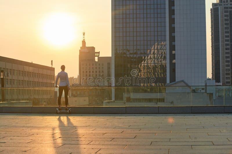 Mujer en el hoverboard, ciudad soleada fotos de archivo