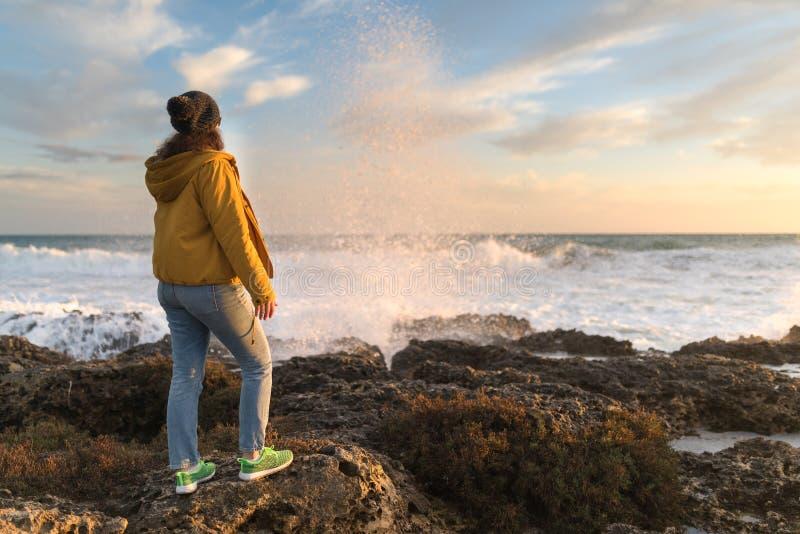 Mujer en el mar en la puesta del sol fotos de archivo