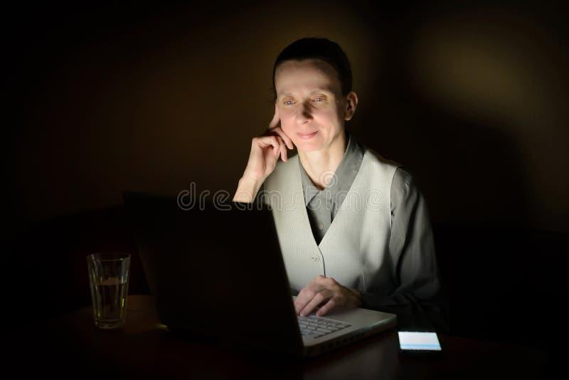 Mujer en el ordenador en la oscuridad fotos de archivo
