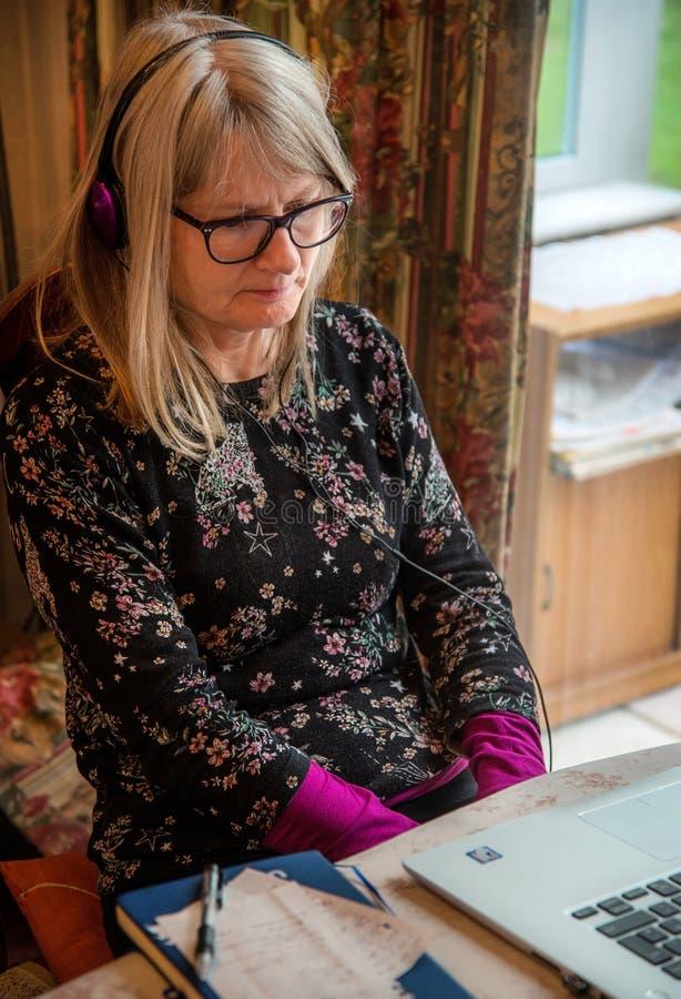 Mujer en el ordenador, observación webinar en su ordenador portátil, auriculares que llevan imágenes de archivo libres de regalías
