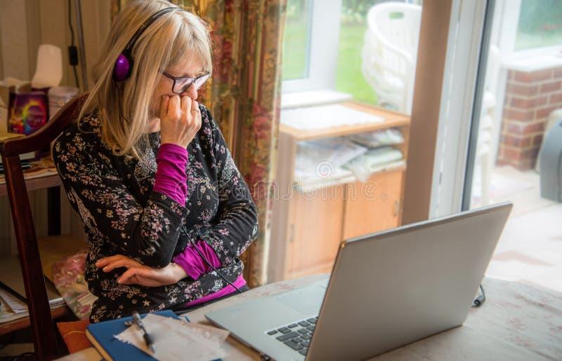 Mujer en el ordenador portátil, trabajando del hogar, mirando un webinar imagen de archivo libre de regalías