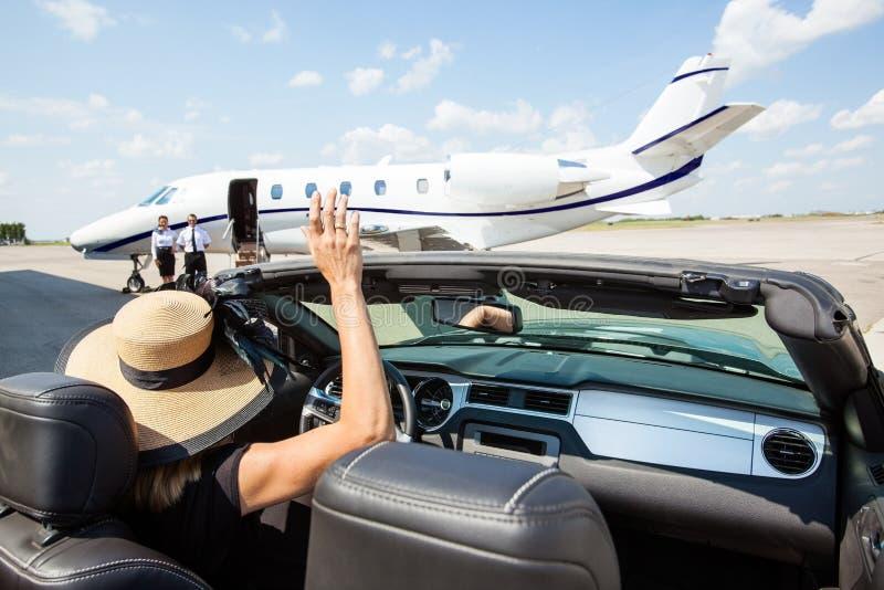 Mujer en el piloto que agita convertible And imagen de archivo libre de regalías