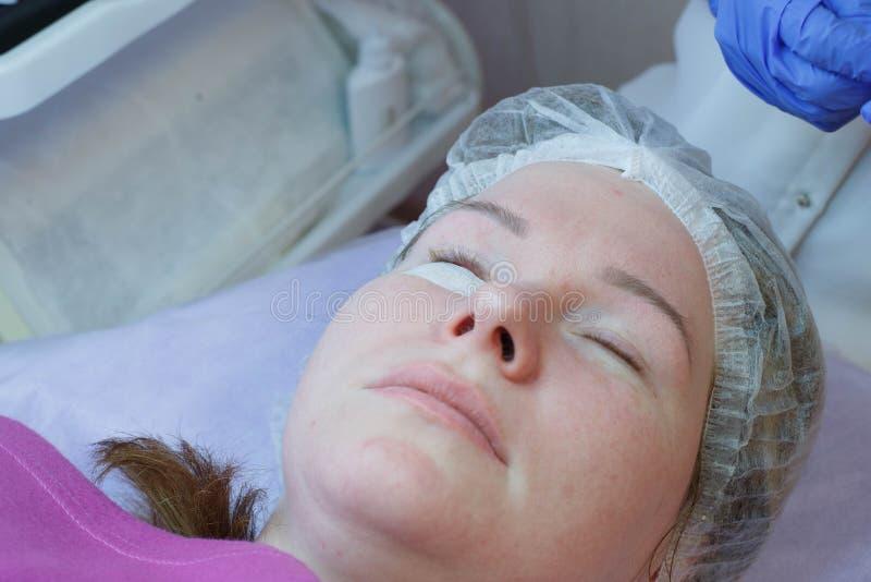 Mujer en el procedimiento para las extensiones de la pesta?a, laminaci?n de las pesta?as imagenes de archivo