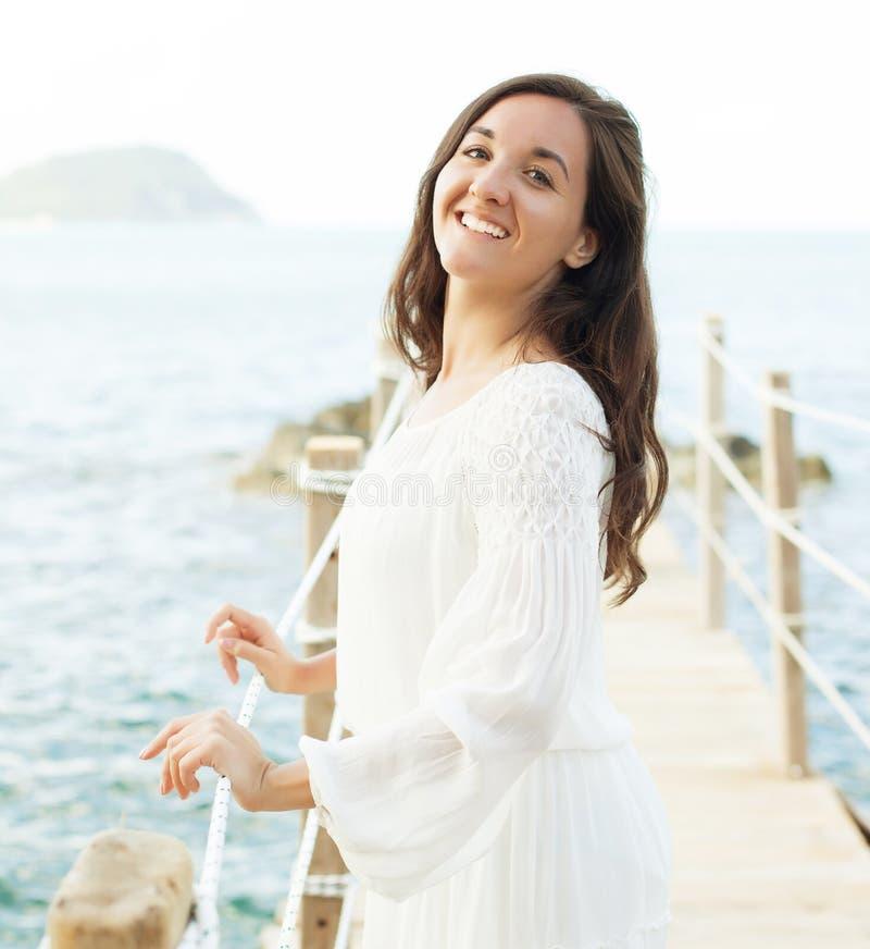 mujer en el puente cerca del mar foto de archivo