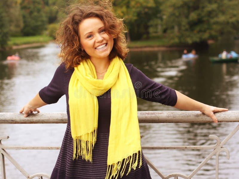 Mujer en el puente en parque del otoño foto de archivo