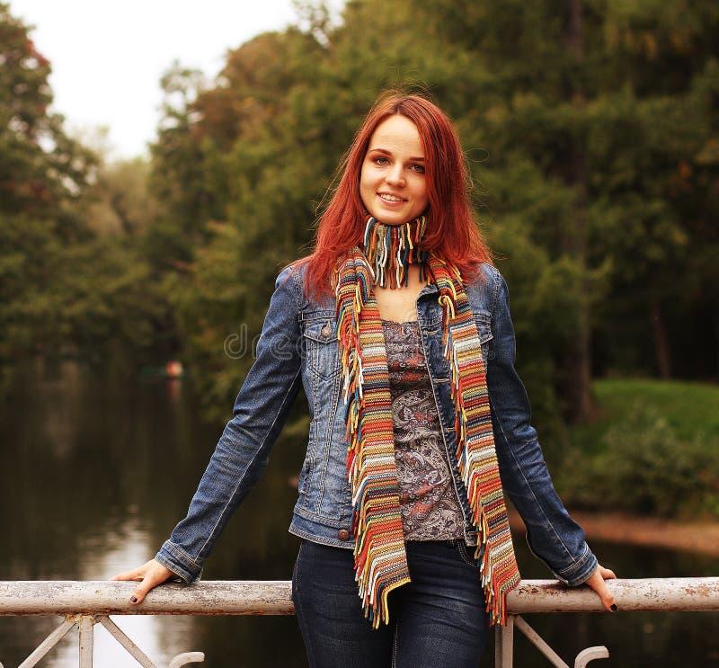 Mujer en el puente en parque del otoño fotos de archivo