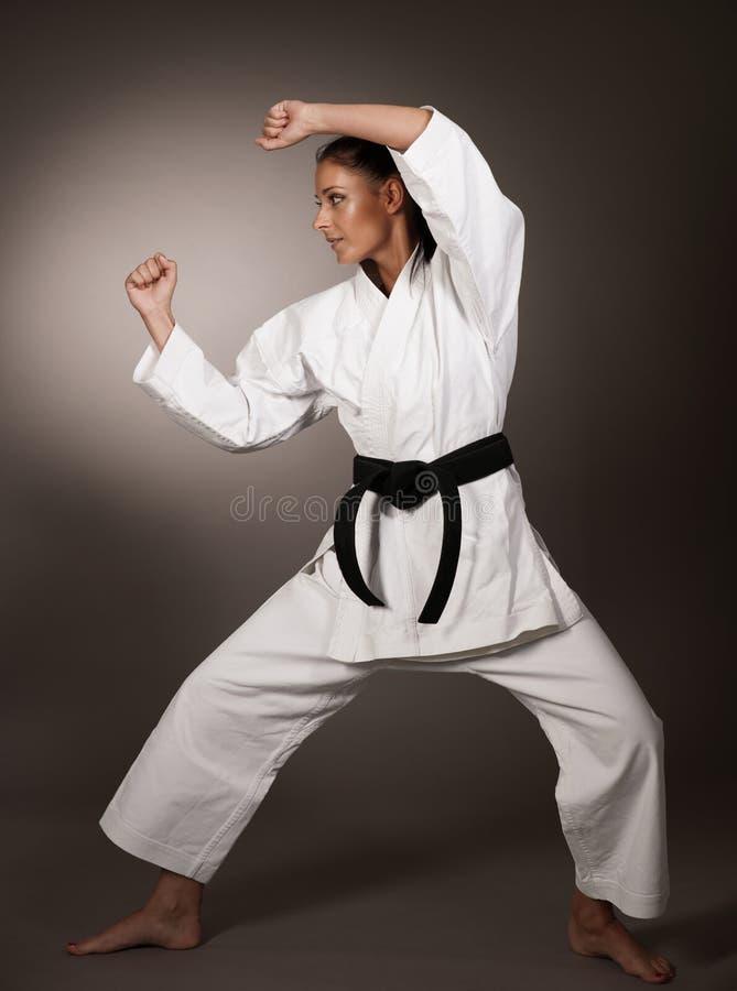 Mujer en el sacador blanco del kimono difícilmente en el aire - muchacha del arte marcial del karate foto de archivo libre de regalías