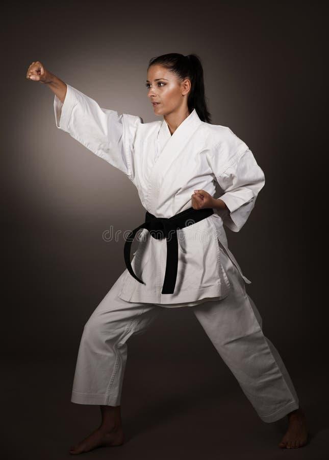 Mujer en el sacador blanco del kimono difícilmente en el aire - muchacha del arte marcial del karate fotos de archivo libres de regalías