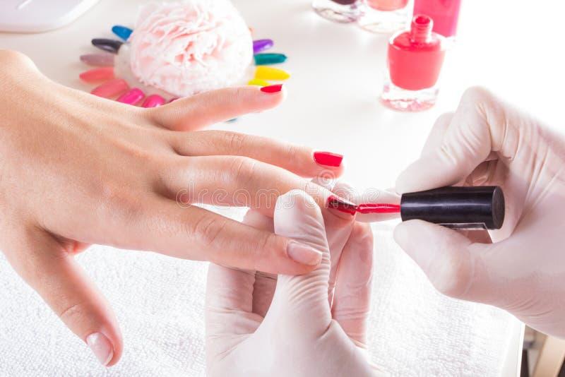 Mujer en el salón del clavo que recibe la manicura del cosmetólogo Primer de la mano femenina que descansa sobre la toalla blanca imagen de archivo