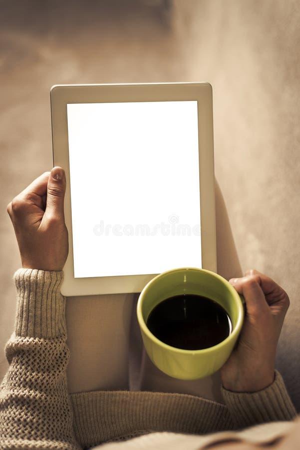 Mujer en el sofá con PC de la tableta imagen de archivo