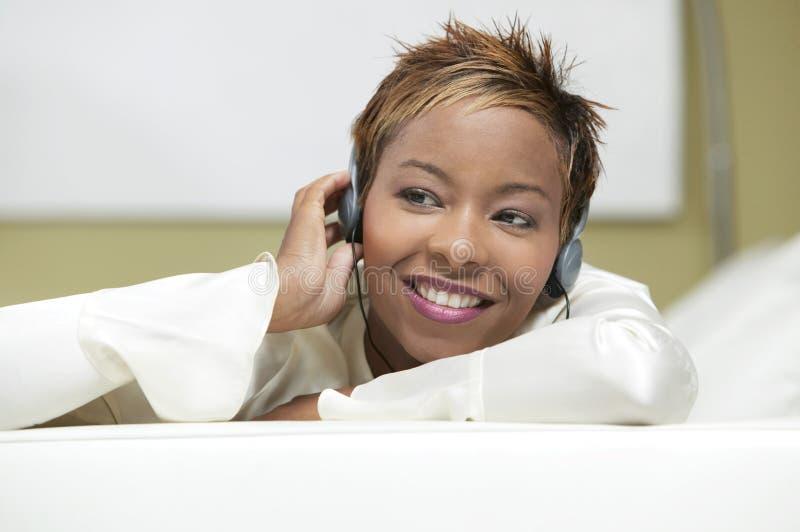 Mujer en el sofá que escucha el cierre de la vista delantera de los auriculares para arriba imagenes de archivo