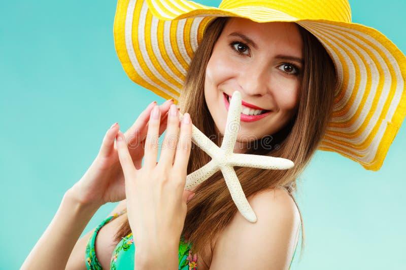 Mujer en el sombrero amarillo que lleva a cabo la cáscara blanca fotos de archivo