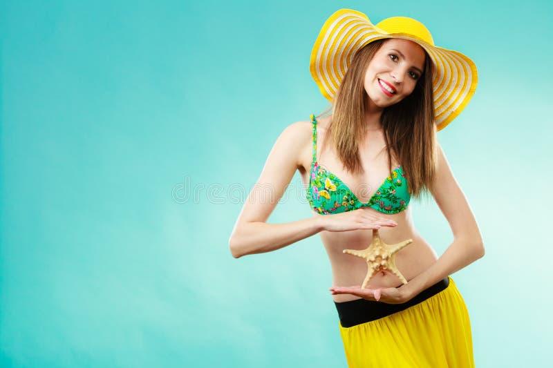 Mujer en el sombrero amarillo que lleva a cabo la c?scara blanca foto de archivo